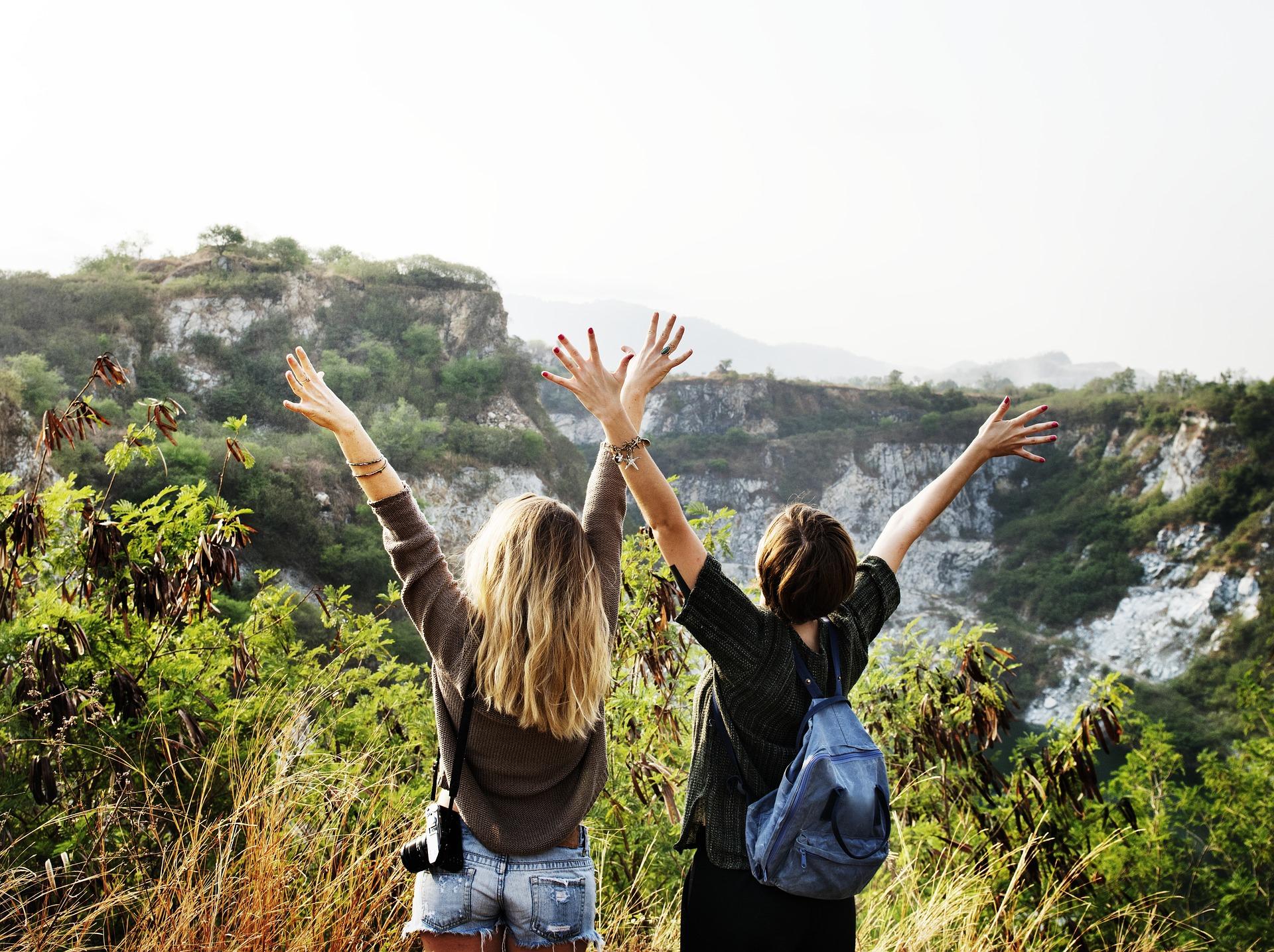 Två tjejer i naturen med armarna uppsträckta