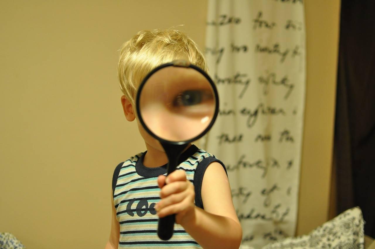 Liten pojke med förstoringsglas