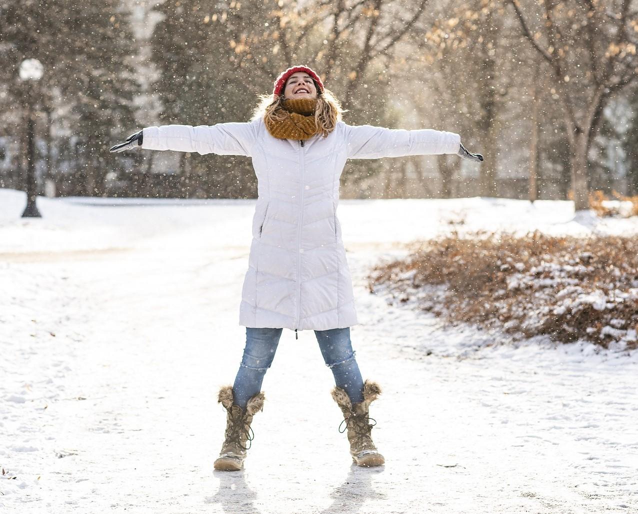 Kvinna med utsträckta armar i vinterlandskap