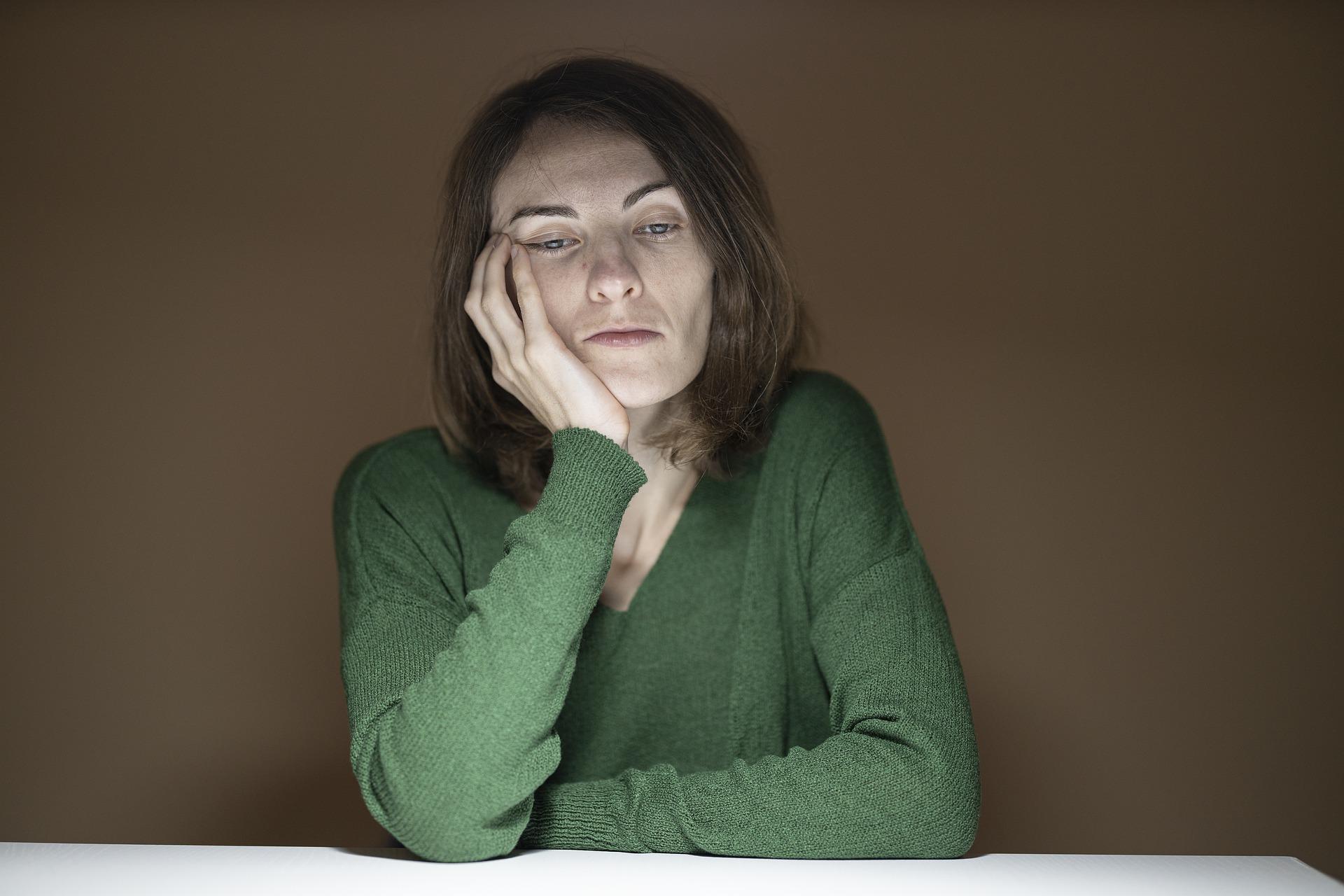 Kvinna som stöder ansiktet i handen och ser trött och uppgiven ut
